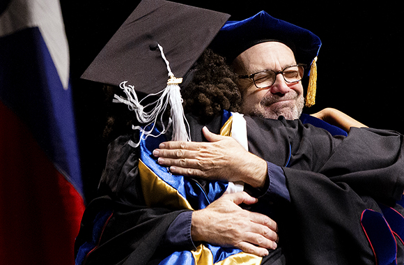 A St. Edward's professor gives his student a big hug after presenting diploma at 2019 Commencement