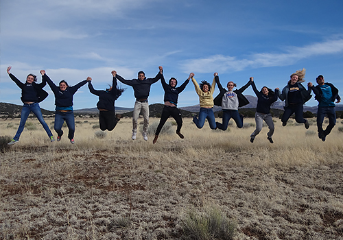Group of tudents jumping in a open field