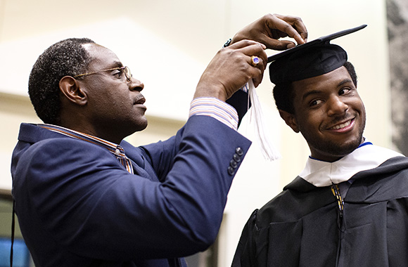 Professor assists a St. Edward's student with his graduation cap and gown