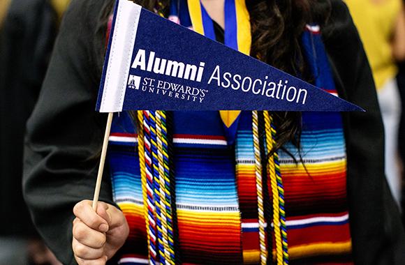 St. Edward's graduate holds SEU Alumni Association flag