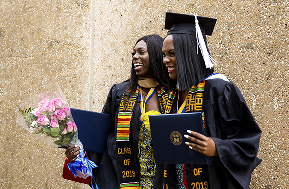 Two St. Edward's graduates pose with flowers and diplomas after the 2019 Commencement Ceremony