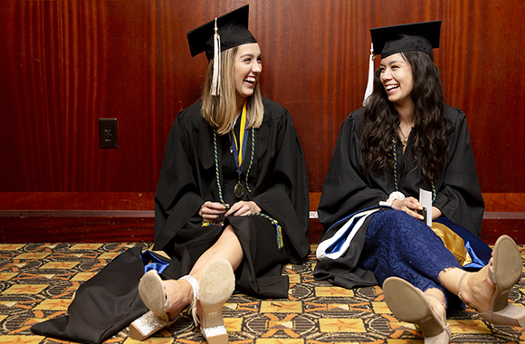 Two St. Edward's graduates chat while sitting on floor backstage as they await the 2019 Commencement Ceremony