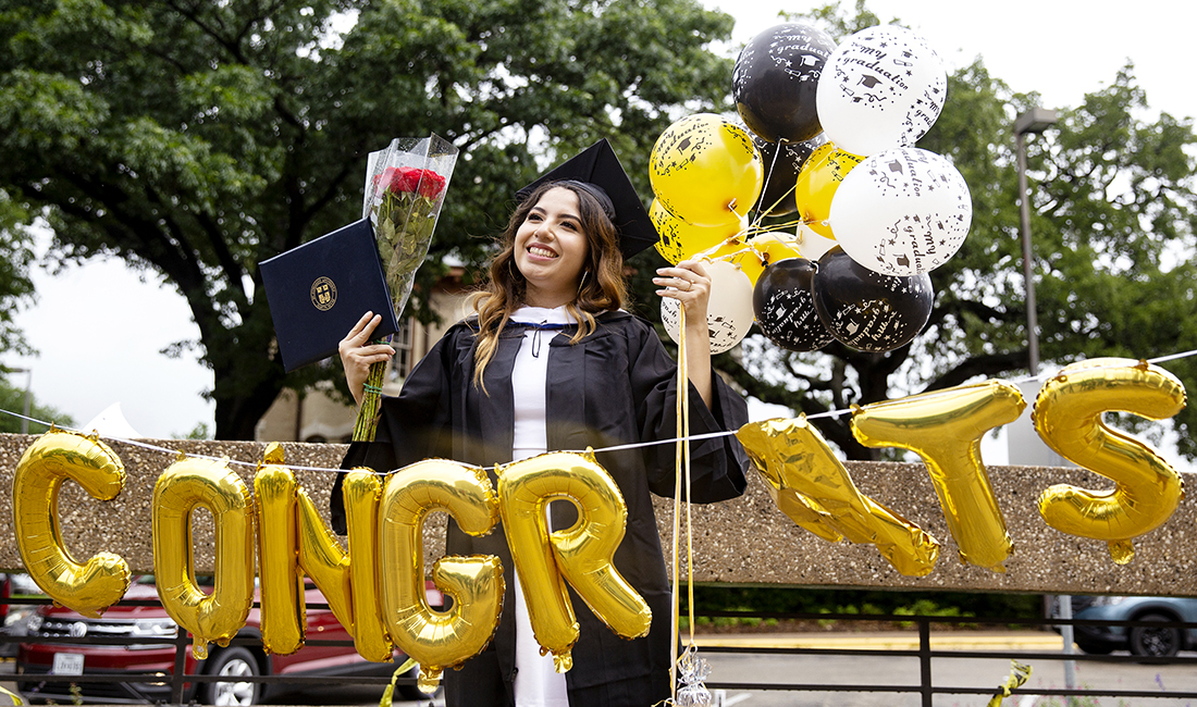 St. Edward's graduate poses with flowers, balloons and her diploma after 2019 Commencement Ceremony