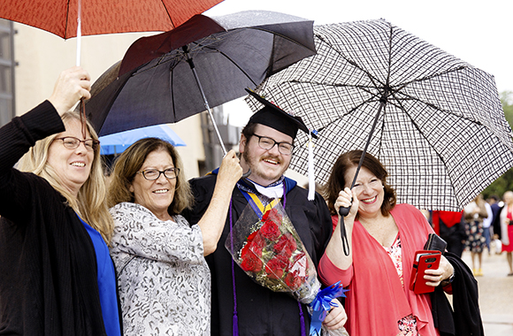 Hilltopper family poses outdoors with umbrellas after 2019 Commencement Ceremony