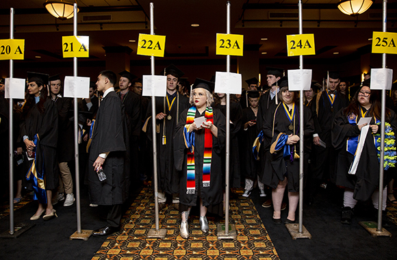 St. Edward's graduates in caps and gowns line up back stage for 2019 Commencement procession