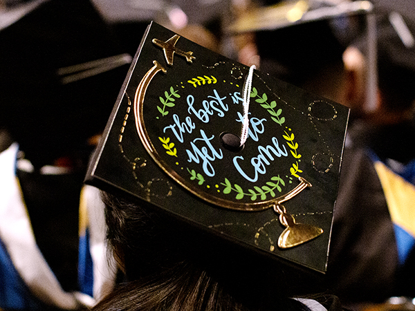A St. Edward's University graudate wears a decorated grad cap at commencement that says The Best Is Yet To Come