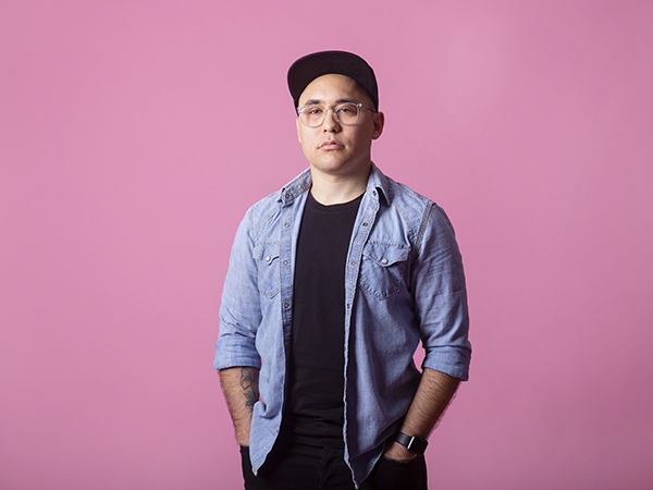 Alum Jake Nishimura stands for a portrait in front of a pink background