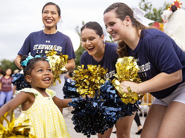 St. Edward's cheerleaders interact with a young girl at Hillfest