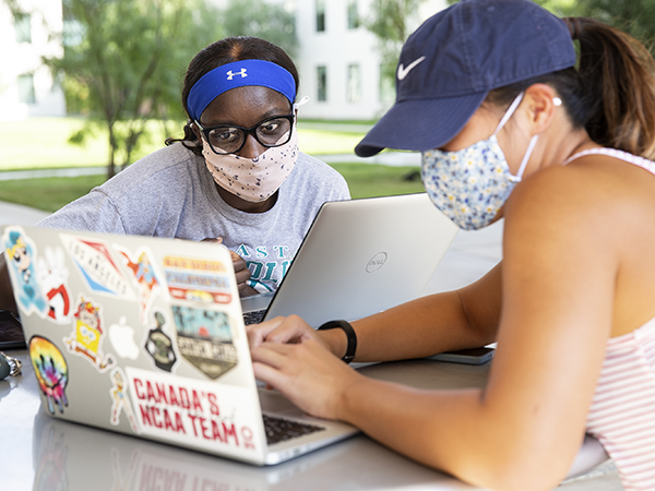 St. Edward's University students wear face masks and study together on laptops outside on a patio
