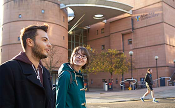 Students walking in front of a building at Abertay University, Dundee, Scotland