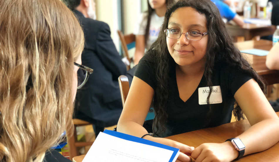 A 10th grader in the Breakthrough program hones her communication skills during an interview with a community volunteer.