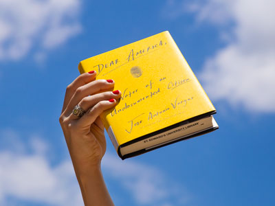 "A hand holds ""Dear America"" book by Antonio Jose Vargas against a blue sky"