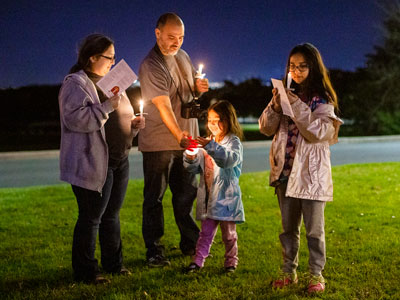 Family lights candles at Festival of Lights