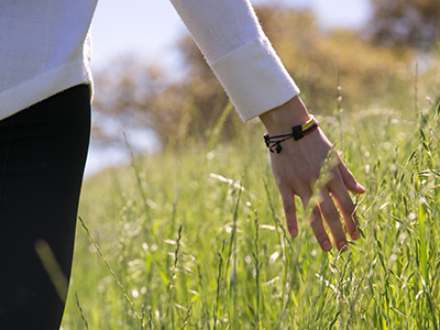 Student walking with her hand toughing tall grass