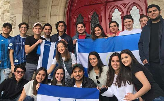 International students with a flag in front of Main building at St. Edward's University