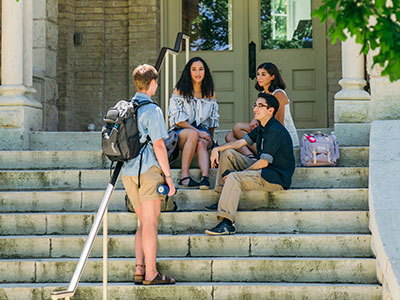 Students chat on the steps of Holy Cross Hall at St. Edward's University