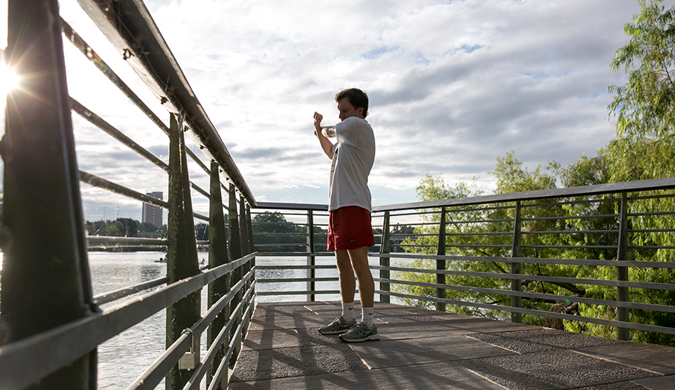 Ben Griffith stretches his arms before starting his morning run at the Ann and Roy Butler Hike-and-Bike Trail and Boardwalk at Lady Bird Lake.