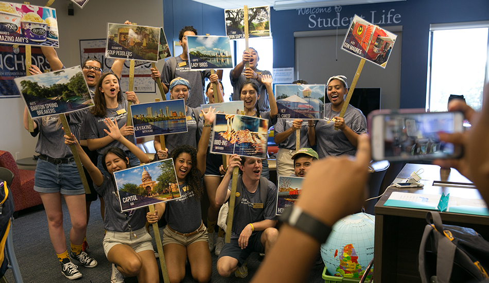 Campus Involvement Team leaders pose for a photo inside the Student Life office while showing off their Austin-themed posters.