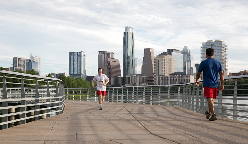Ben Griffith runs along a running trail at Lady Bird Lake with the Austin skyline in the backround.