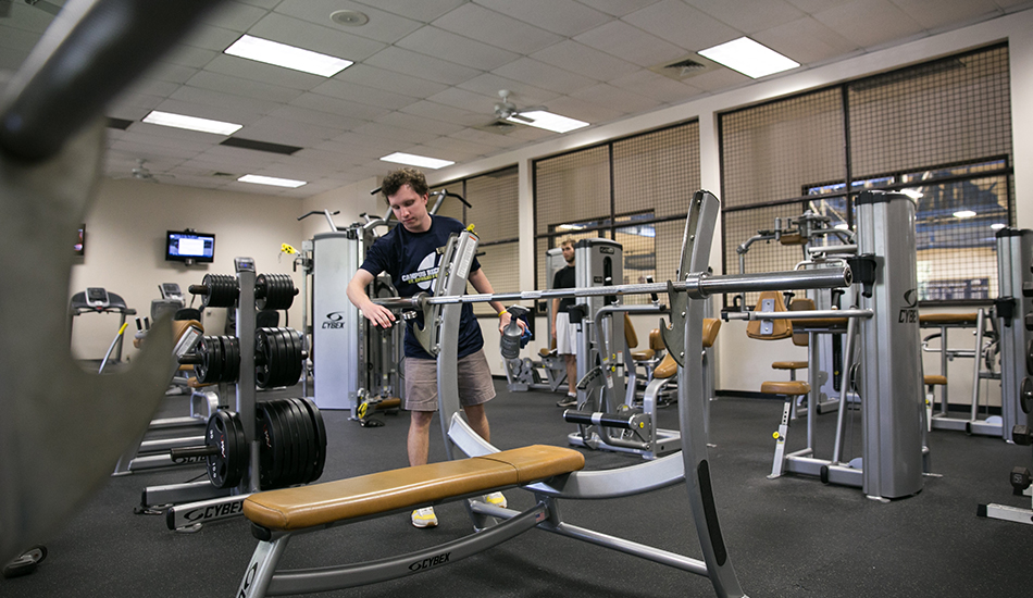"Ben Griffith's cleans equipment inside ""the cage"" at the Recreation and Convocation Center at St. Edward's."