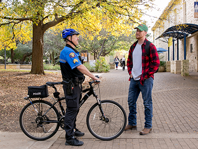 UPD Officer talking with student on campus