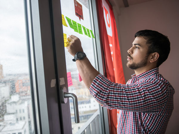 MBA student places Post-It Notes on a window to organize a project.