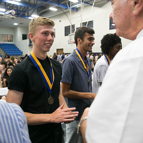 A St. Edward's freshman receives his university medallion during the Medallion Ceremony.