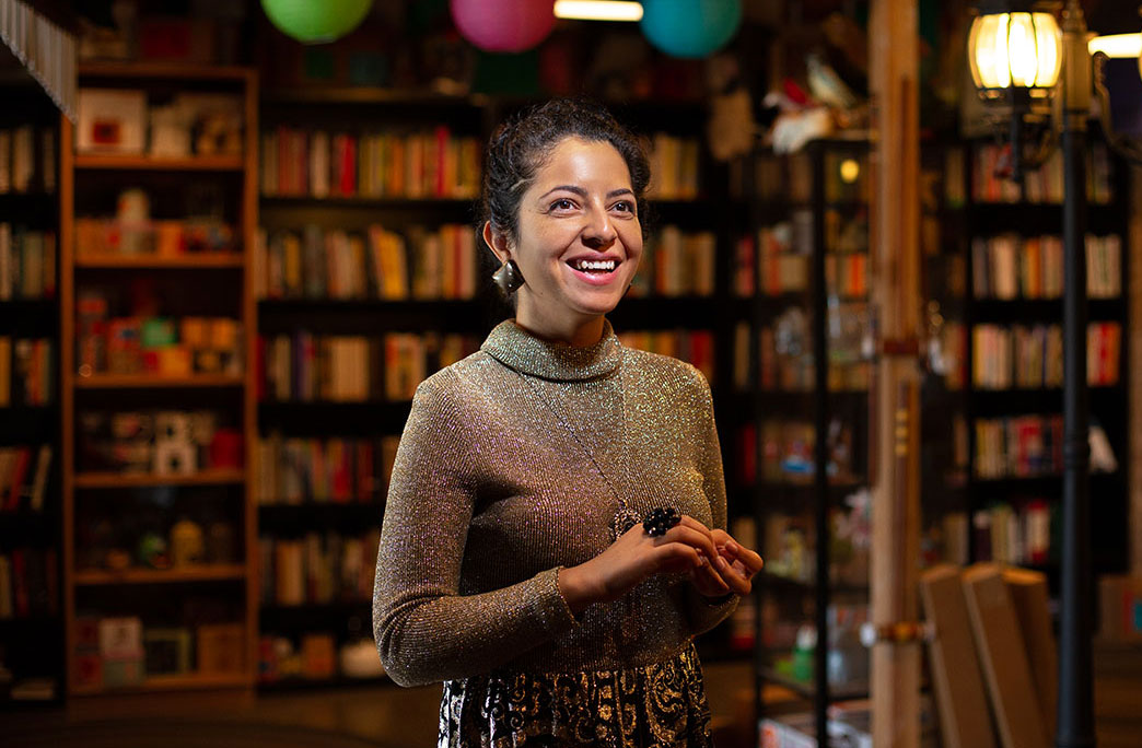 Sara Ortiz standing in the library of the Black Mountain Institute