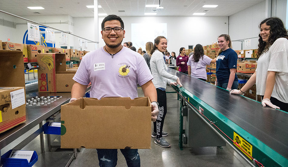 Students from St. Edward's University participate in community service at Capital Area Food Bank
