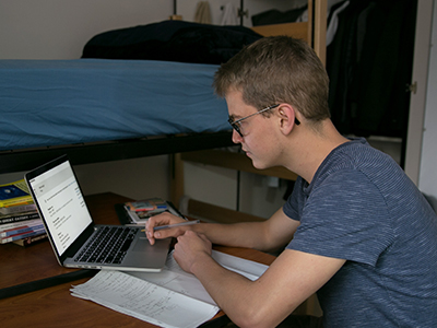 Male student working on laptop in dorm