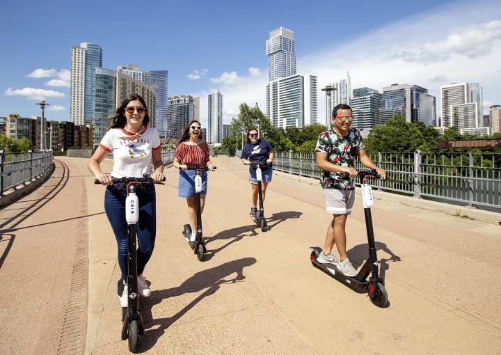 Students riding bird scooters across pedestrian bridge over Lady Bird Lake