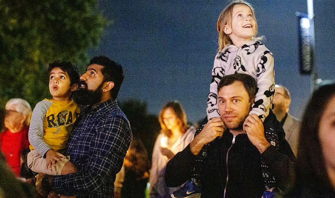 Community members marvel at the light display on Main Building during the festival of lights