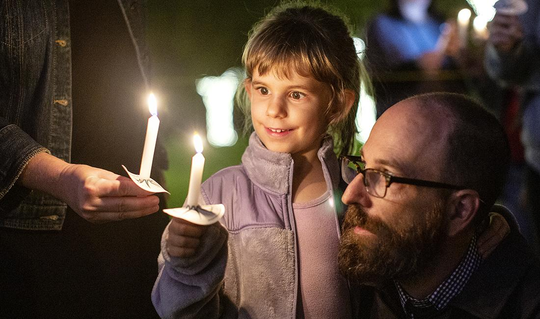 Little girl amazed by candle lighting at Festival of Lights