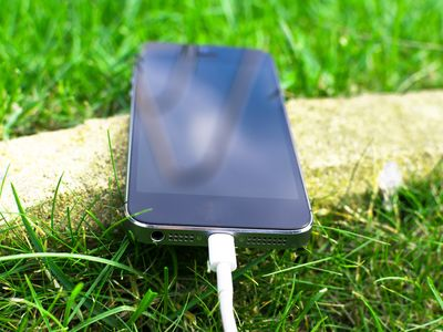 A smartphone with charger cable laying in grass.