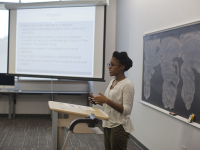 A faculty member stands at a lectern in the front of a classroom with material on a projection screen.