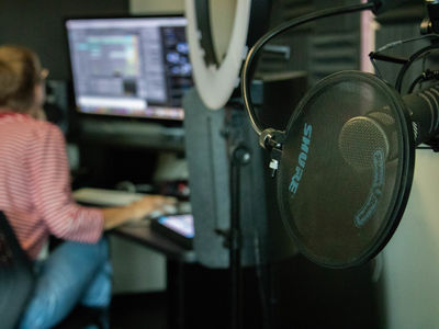 Foreground: studio microphone. Background: Student editing audio on a computer