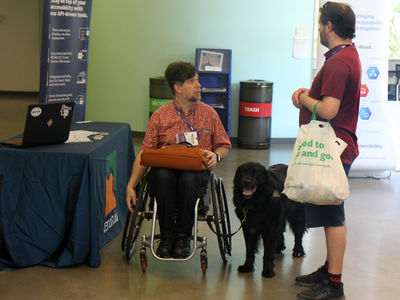 Two AccessU attendees in conversation, with a service dog between them.