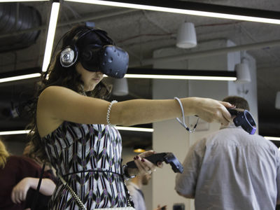 A woman uses a virtual reality headset while pointing a handheld device.
