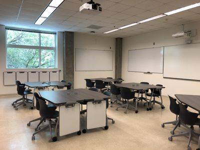 JBWN 202 classroom after renovation with moveable tables and chairs and personal whiteboards lined up along the wall.