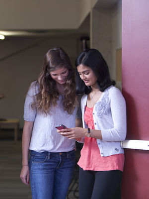 Two students look at a smartphone while hanging out in a doorway.