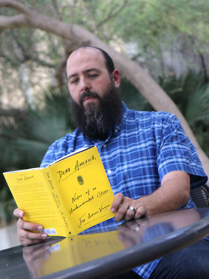 Jason Arellano reads Dear America at an outside table.