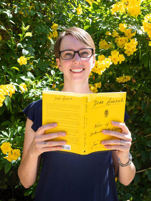 Johanna Jones holds up her copy of Dear America in front of a bush with yellow flowers.