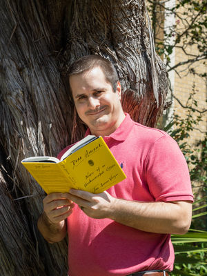 Brant Christiansen leans against a tree with his copy of Dear America.