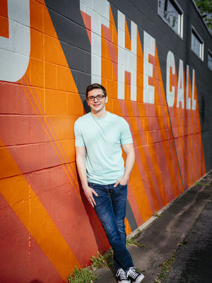 "Josh leans on a wall with an orange, red and black mural. Text behind him reads ""The Call."""