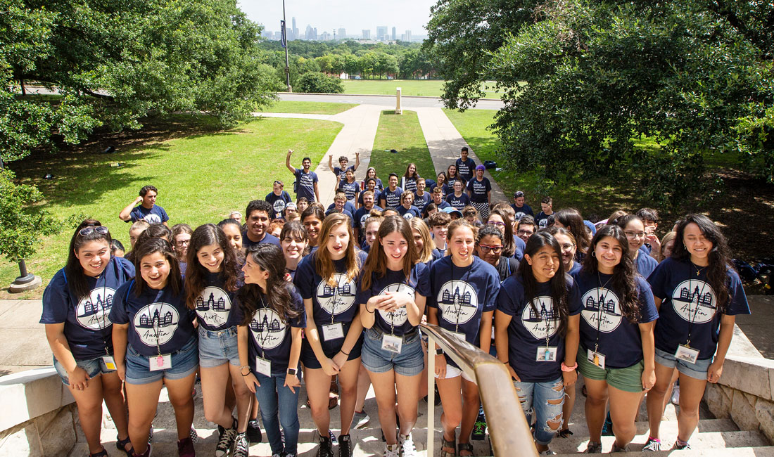 Class of 2023 climbs the steps of Main Building with Austin skyline in the background.