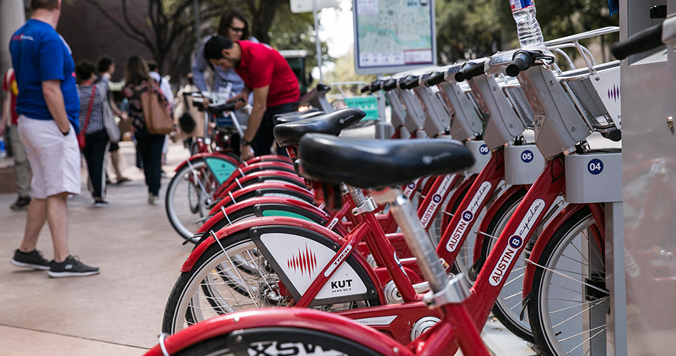 Red bilkes are lined up at one of many downtown Austin Rent-a-Bike stands.