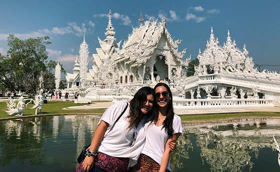 Two students in front of a landmark in Thailand