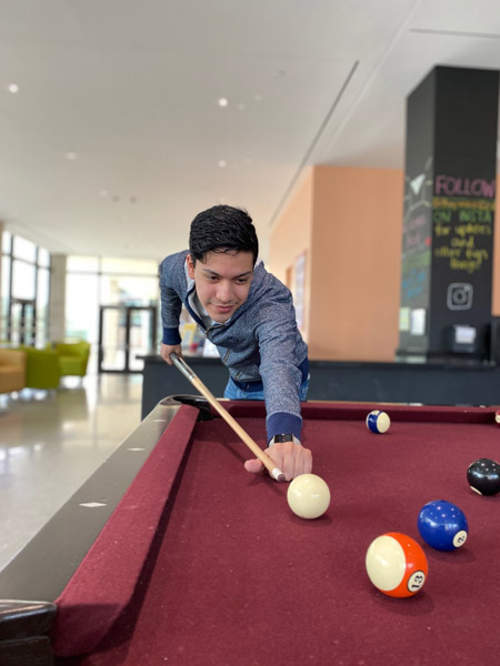 Tony plays pool in his residence hall.