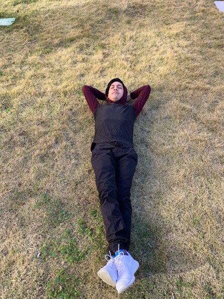 Tony lays on the grass on a nice day outside of his residence hall.