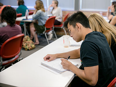 An undergraduate student takes notes in class of peers